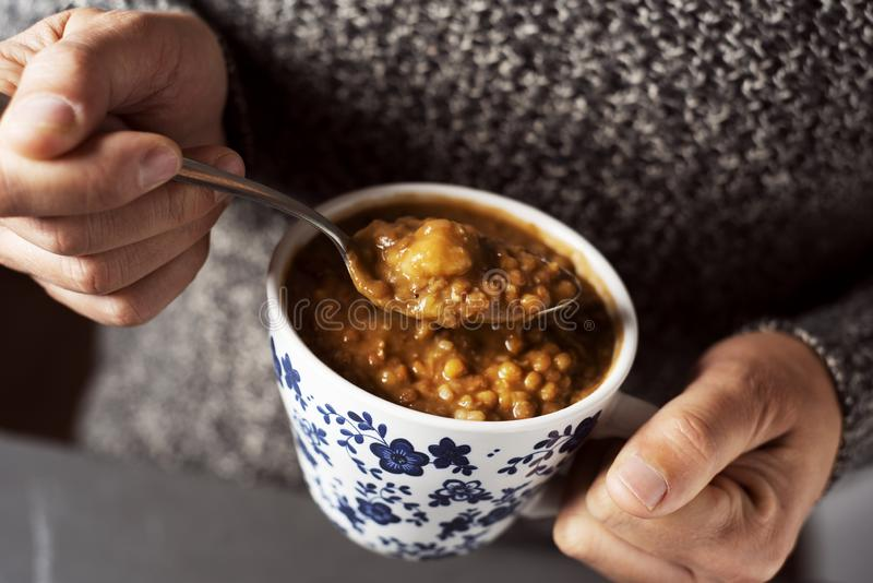Man eating a lentil soup. Closeup of a young caucasian man eating a warming lentil soup from a white and blue ceramic bowl stock images
