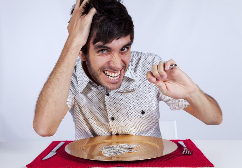 Man eating little dollar banknote stock image