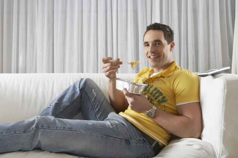 Man Eating Noodles From Takeaway Tray At Home royalty free stock image