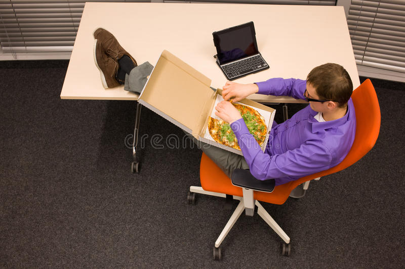 Man eating pizza in office stock photo