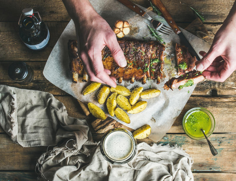 Man eating roasted pork ribs with garlic, rosemary, potato. sauce. Man eating roasted pork ribs with garlic, rosemary, fried potato and green herb sauce on stock photography