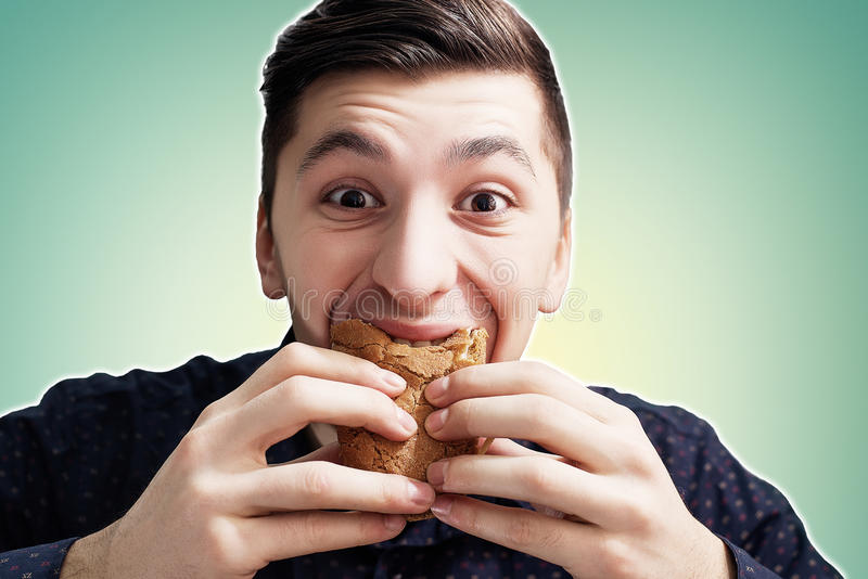 Man eating a sandwich with violent impetuosity stock photography