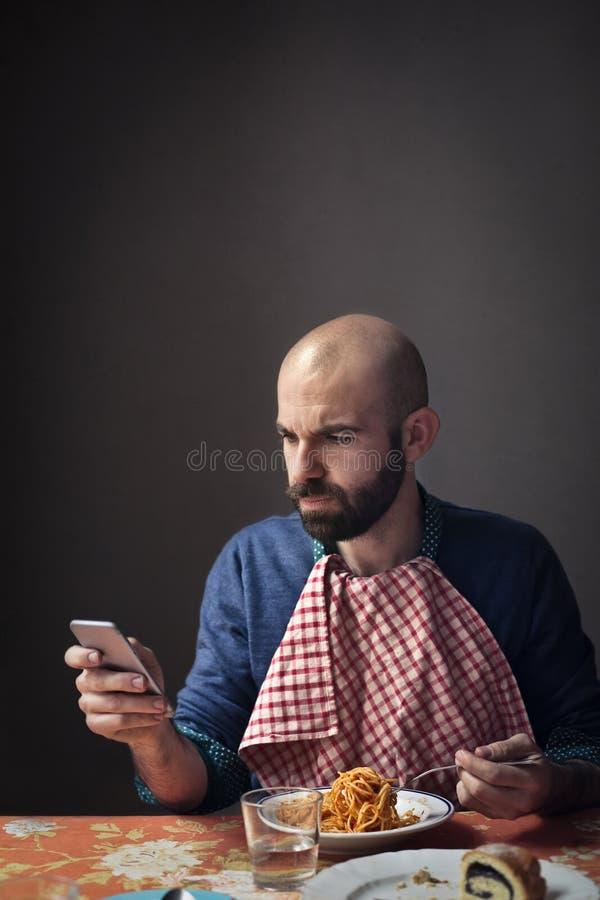Man eating spaghetti and using phone. Man checks his phone while eating pasta royalty free stock images