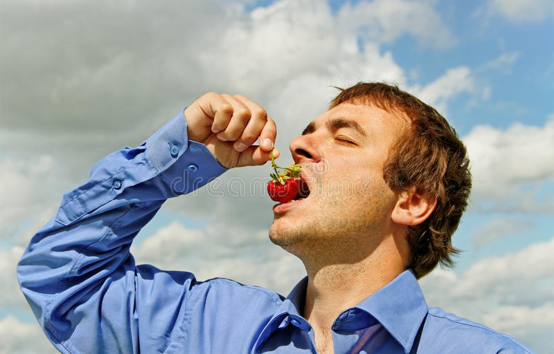 Man eating strawberry. stock photography