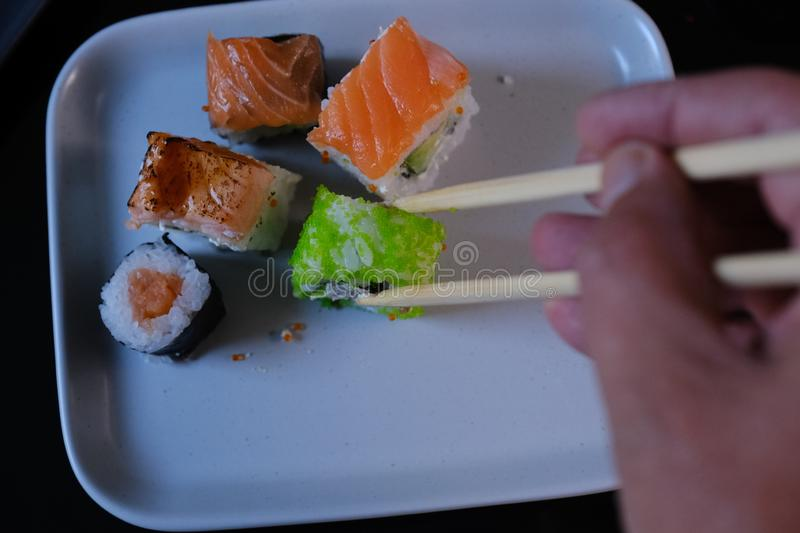 Man eating sushi roll with salmon and flying fish caviar on a black table. Sushi roll with seafood and soy sauce, wasabi and stock images