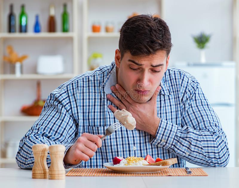 Man eating tasteless food at home for lunch royalty free stock images
