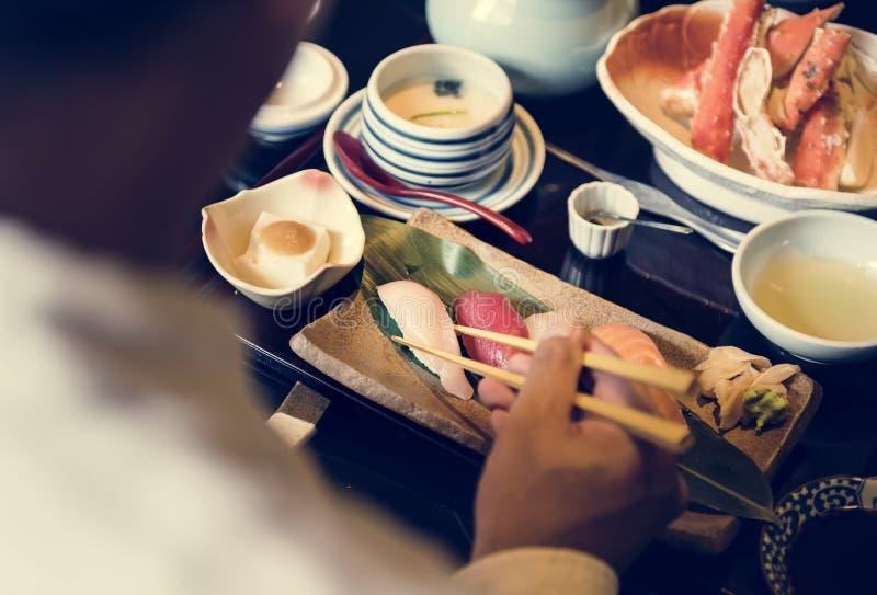 Man eating traditional Japanese food stock image