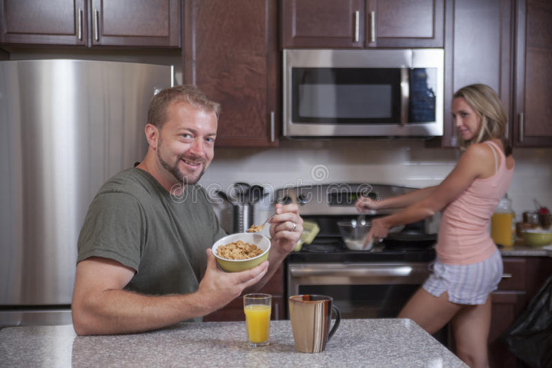 Man eats cereal while lady makes breakfast stock photos