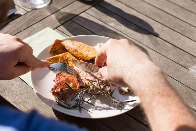 Man eats a cooked steak with vegetables on the grill royalty free stock image