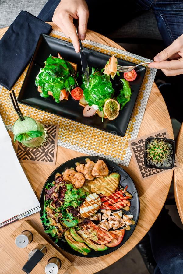 Man eats delicious savory breakfast. Waffles on a black plate on a wooden table in restaurant. royalty free stock images