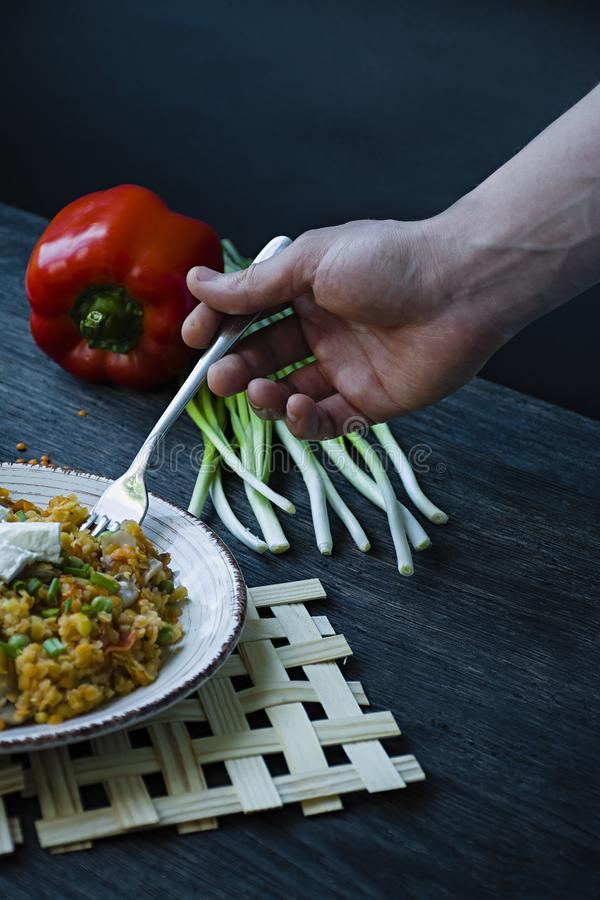 A man eats a lentil porridge with vegetables and greens and fett cheese. Healthy lifestyle. Dietary menu. Dark wooden background. stock images