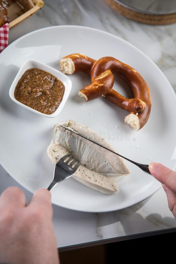 Man eats Munich white sausage with knife and fork, sweet mustard and pretzel and take off sausage properly out of gut. On porcelain plate royalty free stock photography