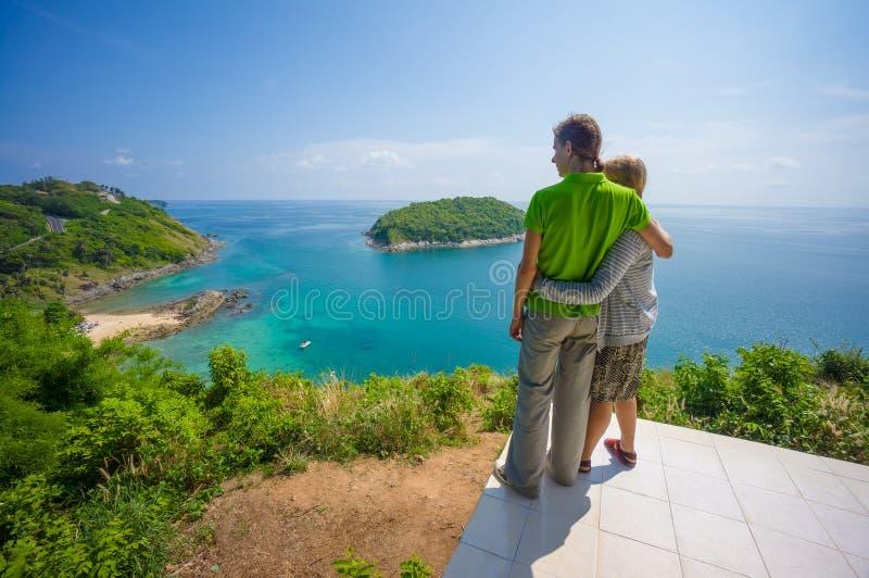 Man ed abbracci della donna sulla scogliera tropicale dell'isola con la piccola spiaggia fotografia stock