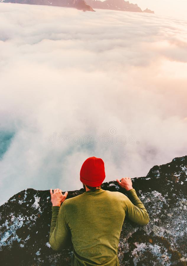 Man on the edge cliff above clouds gaze into abyss royalty free stock photography