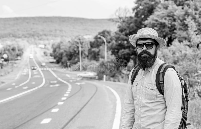 Man at edge of highway looking for transport. On the road. Hitchhiking means transportation that gained asking strangers. For ride in their car. Hitchhiker try stock photos