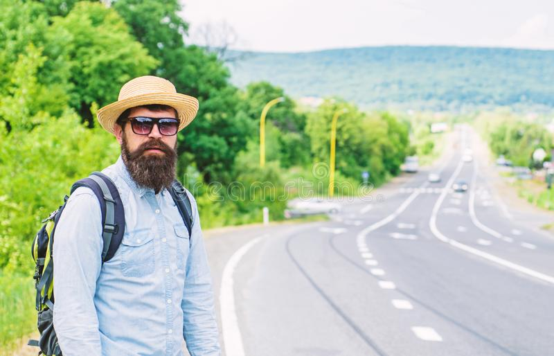 Man at edge of highway looking for transport. On the road. Hitchhiking means transportation that gained asking strangers. For ride in their car. Hitchhiker try royalty free stock photo