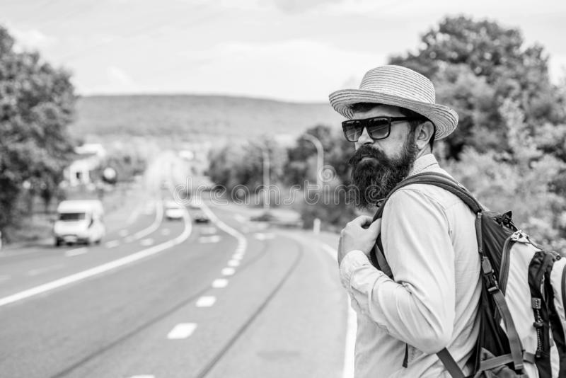 Man at edge of highway wait transport. Travel alone. Hitchhiking means transportation gained asking strangers for ride stock photos