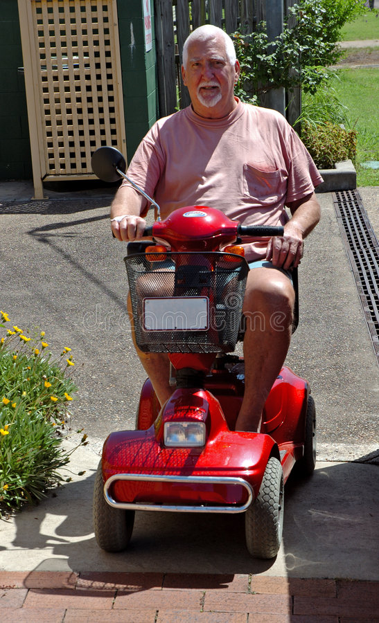 Man on Electric buggy #2. An electric buggy used when the legs just won't go that far any more royalty free stock image