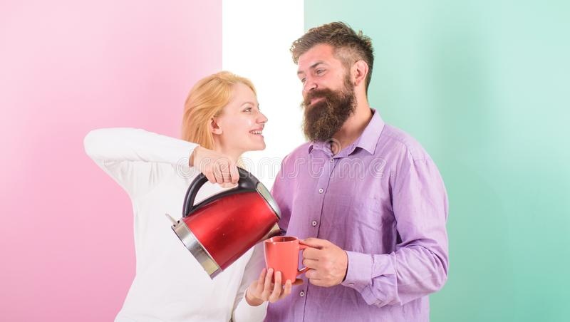 Man with electric kettle and woman with mug ready to drink morning coffee. Enjoying nice morning together. First thing. Man with electric kettle and women with stock image