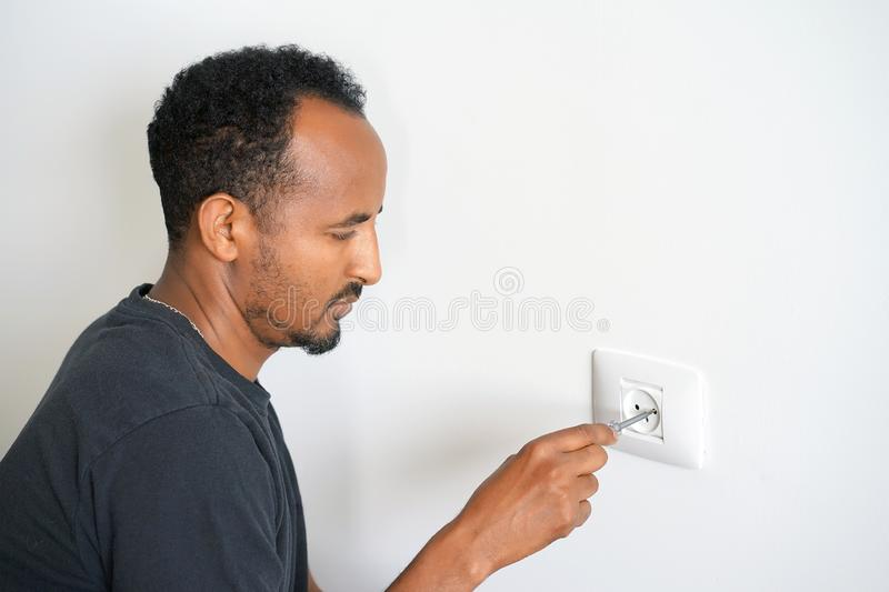 An electrician checks the voltage in the wall socket stock photos