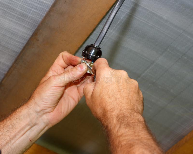 Maie electrician installs an electric lamp holder stock image