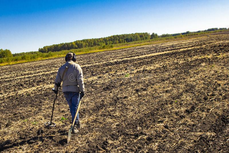 Man with electronic metal detector device working on outdoors background. Close-up photography of searching process. Man with electronic metal detector device stock photography