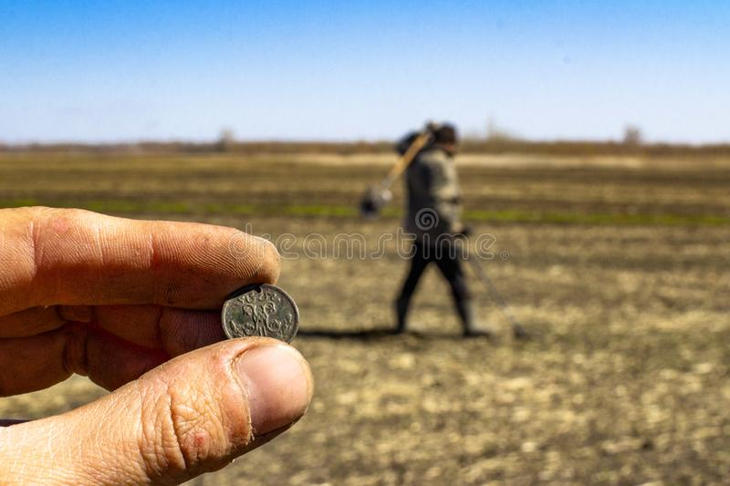 Man with electronic metal detector device working on outdoors background. Close-up photography of searching process. Man with electronic metal detector device royalty free stock photo