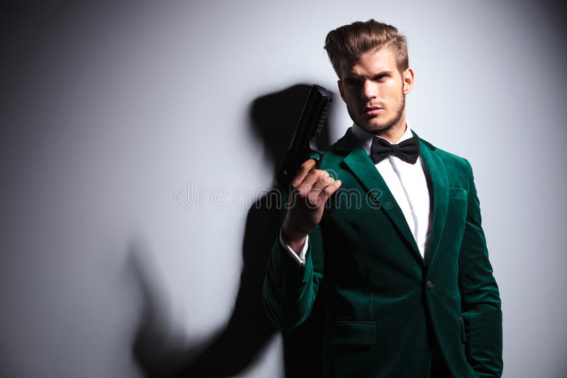 Man in elegant green velvet suit holding a big gun. Young man in elegant green velvet suit holding a big gun and looks away from the camera royalty free stock photography