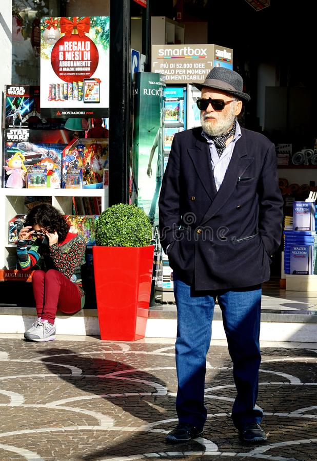 Man in elegant jacket. Civitavecchia Rome Italy An elderly gentleman dressed elegantly with a hat, jacket and sunglasses. waiting holds his hands in his pockets royalty free stock photos