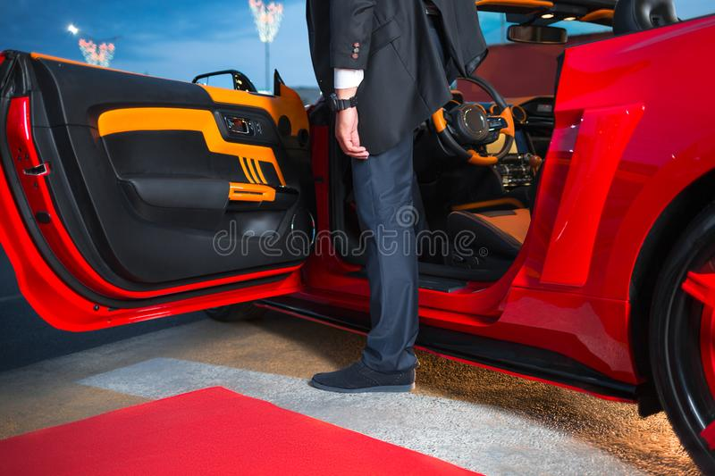 A man in an elegant suit exiting red supercar to red carpet event. stock photo