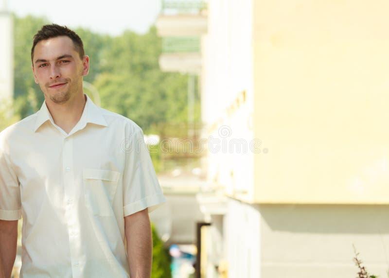 Man in elegant white summer shirt outside. stock photo