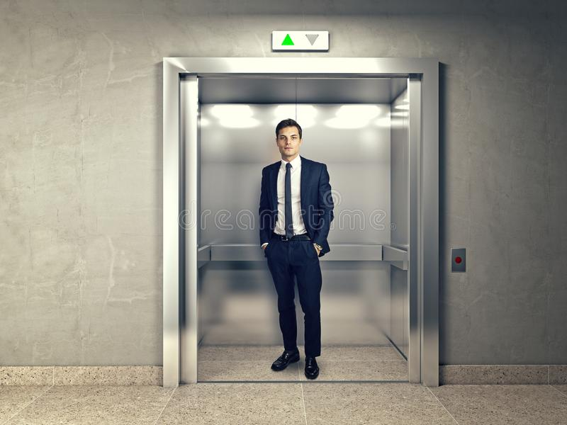 Man in elevator. Standing young businessman in modern elevator royalty free stock photos