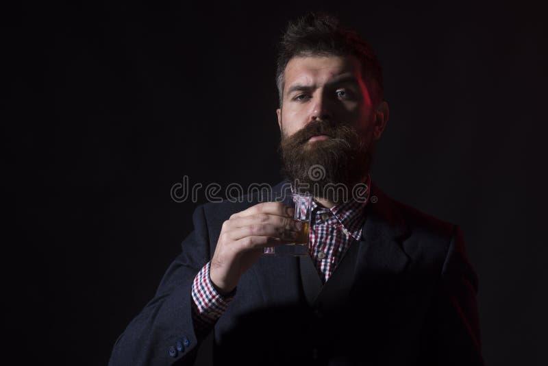 Man- eller affärsmandrinkwiskey på svart bakgrund arkivbilder