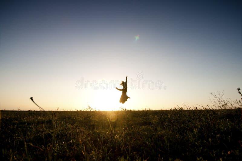 Man eller kvinna i kontur mot solnedgången som hoppar och har gyckel lycka- och frihetsbegreppet för folk tycker om det utomhus- royaltyfria bilder