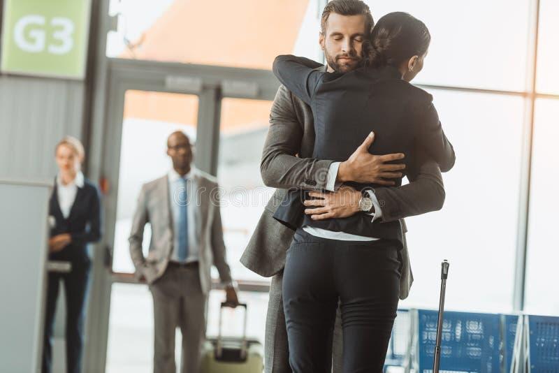man embracing woman at airport after stock photography