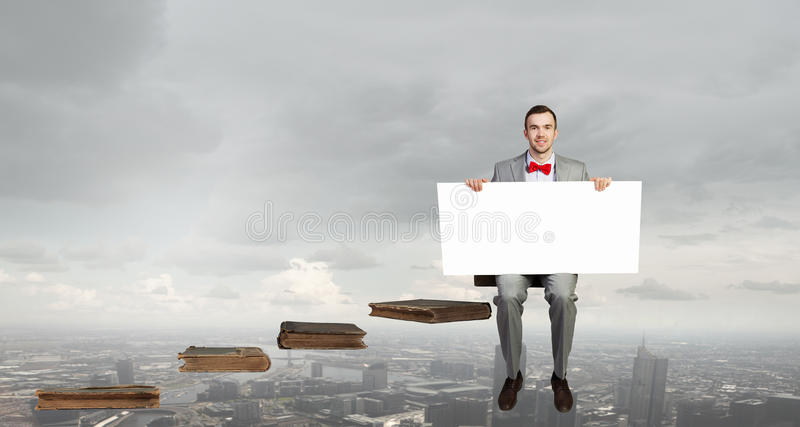 Man with empty banner. Young businessman sitting on book holding white blank banner in modern office stock photos