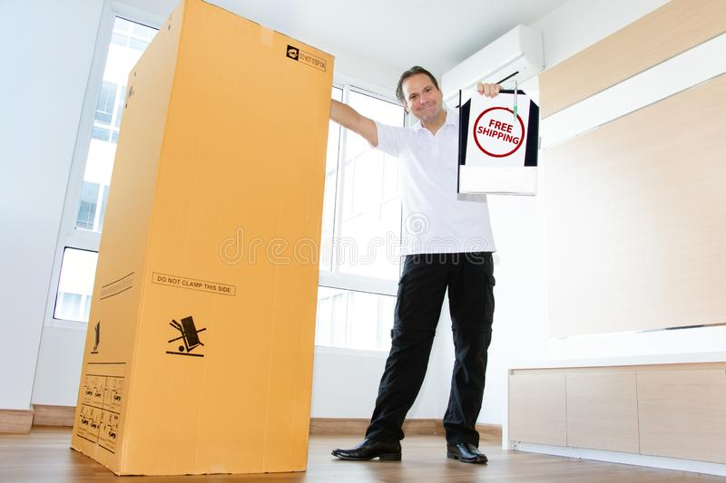 The postman with ree shipping large package. A man in an empty room shows a paper document with stamp for free shipping large package. The postman delivers the stock image