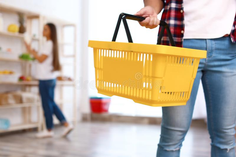 Man with empty shopping basket in grocery store. Closeup stock photography