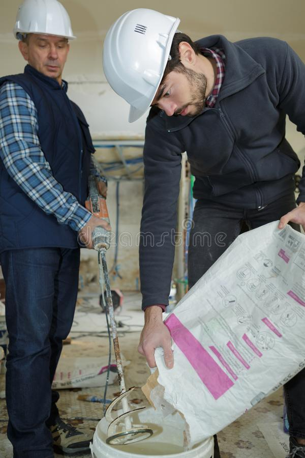 Man emptying cement into tub to mix. Cement royalty free stock photography
