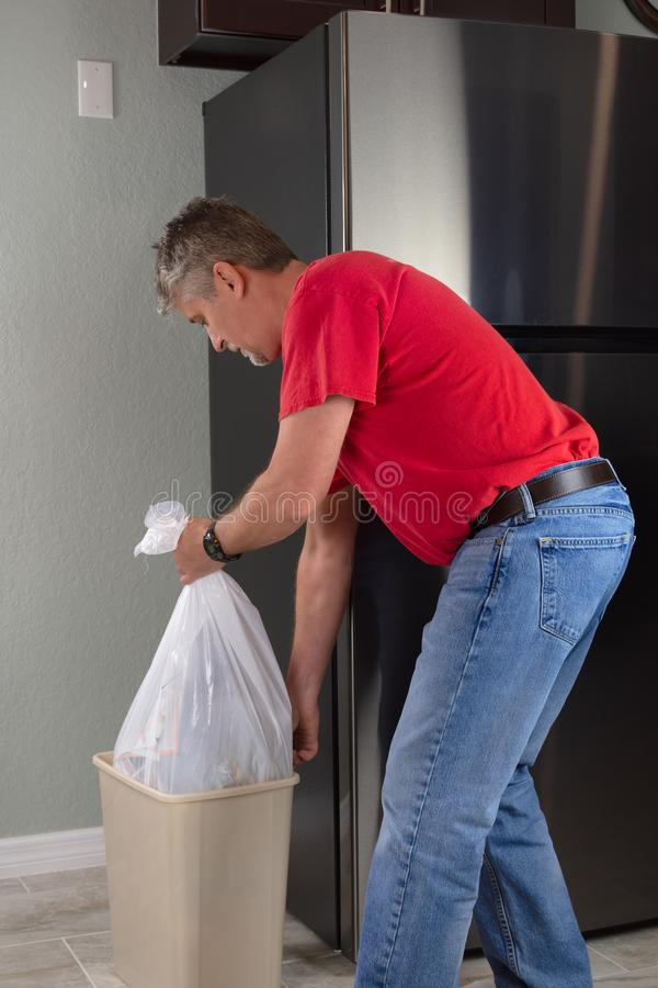 Man emptying trash bag bin container in kitchen to take it out to garbage can stock photo