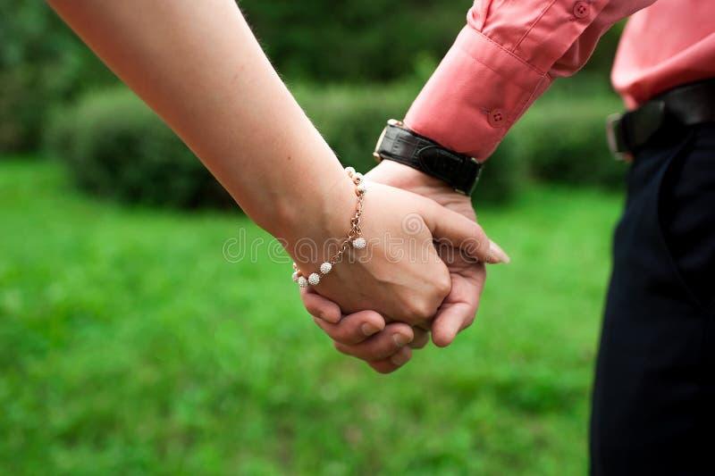 Man en een vrouw met de handen van een armbandholding strak royalty-vrije stock afbeelding