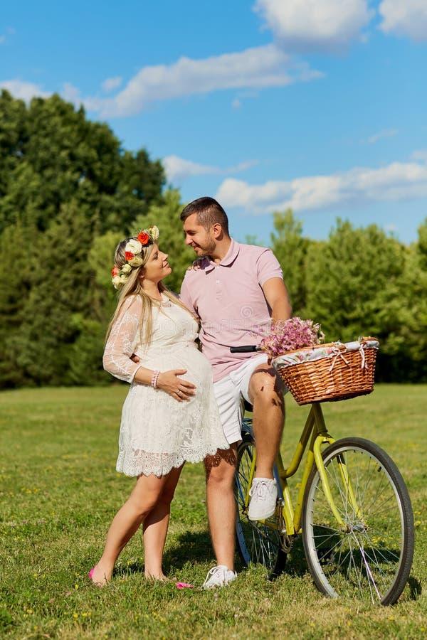 Man en een zwangere vrouwen gelukkige aard in park Jonge gelukkige famil royalty-vrije stock afbeeldingen