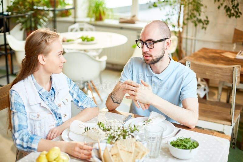 Man en jonge vrouw die in koffie spreken stock foto's