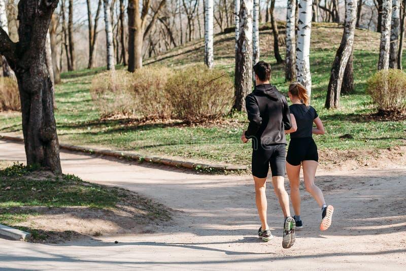 Man en jonge vrouwenatleet in de sportkledingszomer vroege ochtend die in Park lopen Gezond levensstijlconcept Achter mening royalty-vrije stock fotografie