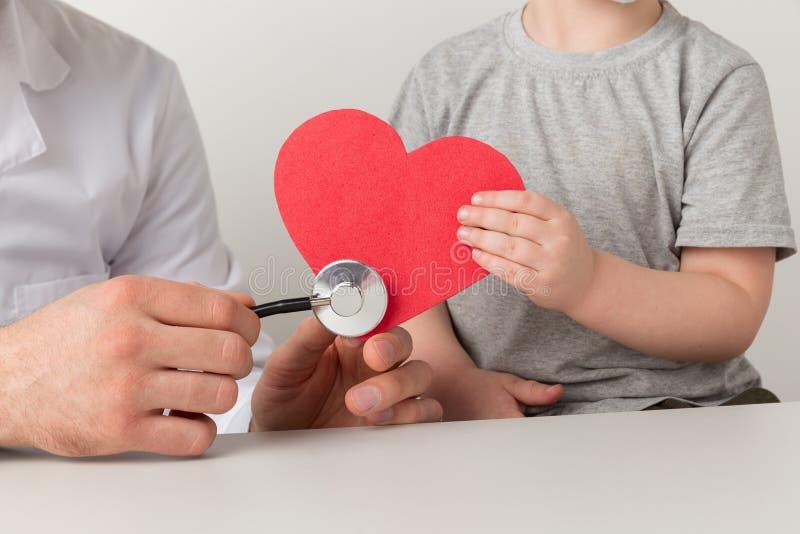 Man en kind luisteren naar het hart met stethoscoop Uw gezondheidsconcept ondersteunen stock foto