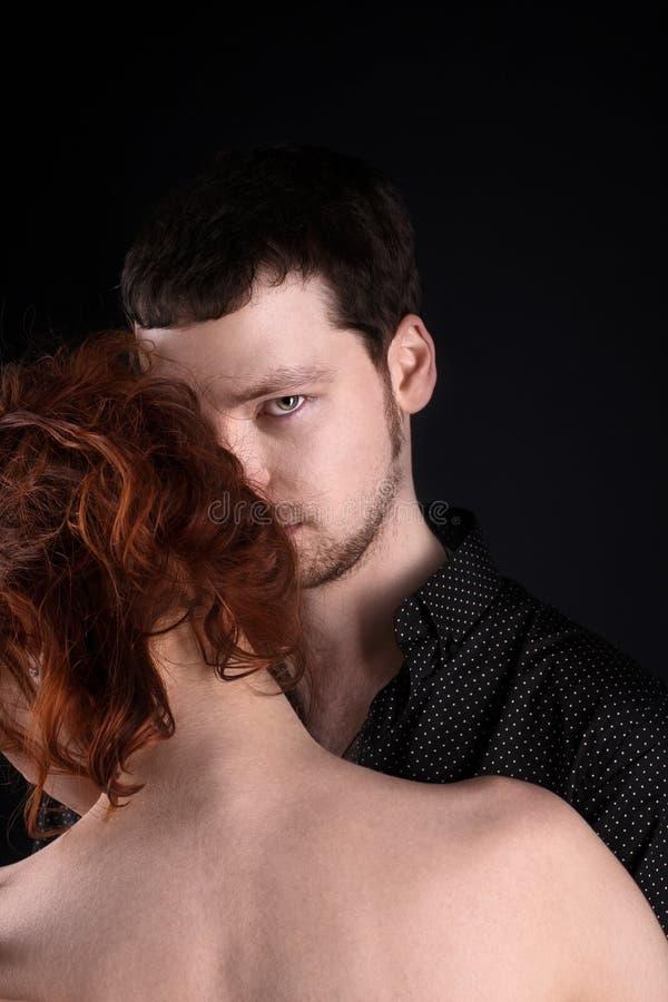 Man en rode vrouw - minnaarsportret stock afbeelding