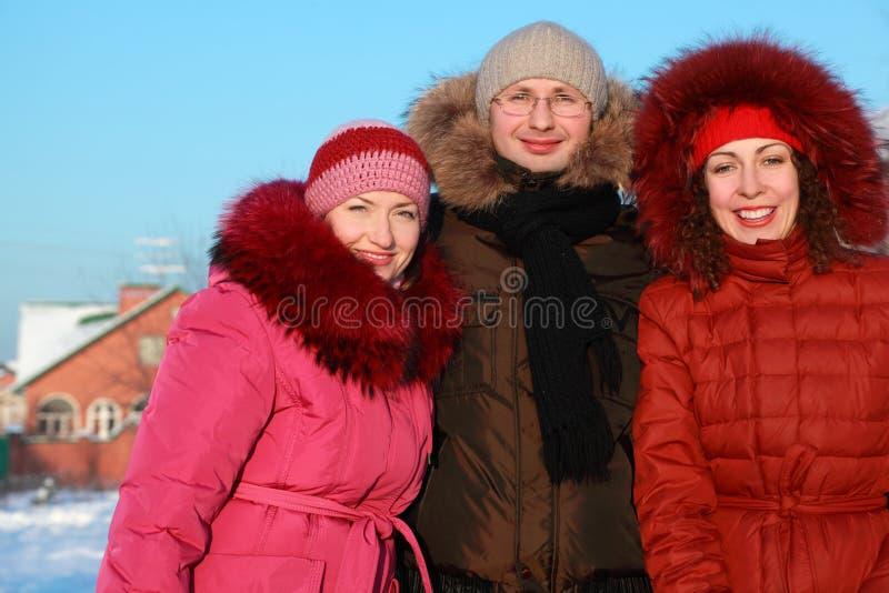 Man en twee vrouwen die zich in openlucht in de winter bevinden stock foto