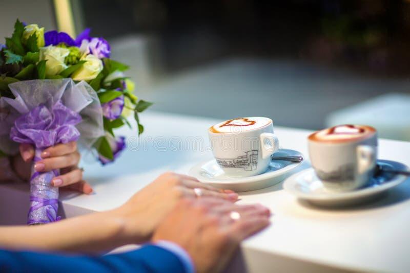 Man en van de vrouw handen met espousal ringen, koffie, huwelijk royalty-vrije stock afbeeldingen
