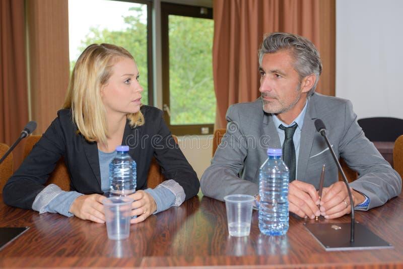 Man en vrouw bij conferentiebureau dat wordt gezeten royalty-vrije stock foto