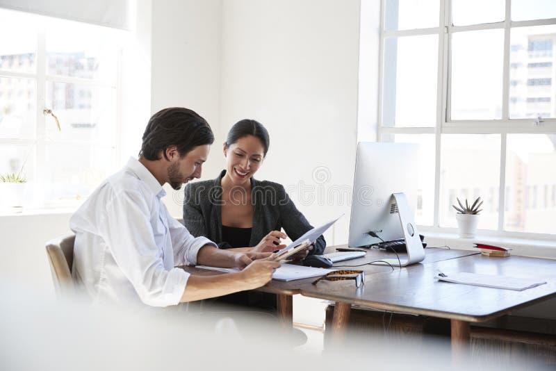 Man en vrouw bij een bureau in een bureau die documenten bekijken stock foto